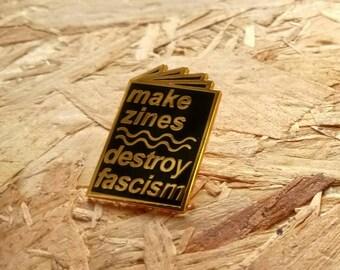 Make Zines Destroy Fascism enamel pin in gold and black