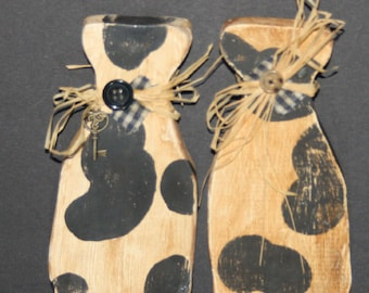 Two primitive milk bottles cut from wood. Distressed woo. Cow pattern