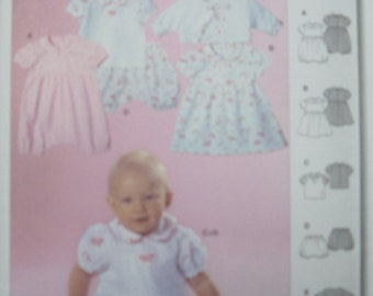 Burda 9752. Semi-fitted infant outfit in sizes 1 month - 12 months. Adorable little jumpers, dress, top, shorts, and jacket. New, uncut.