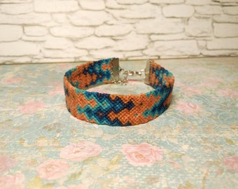 Friendship woven bracelet. Arrowhead patterned. Macrame. Thread, Knotted. Braided. Bright colors. Blue. Orange. Wrist band