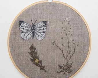 Handmade embroidered botanical illustration: butterfly, shepherd's purse plant and  yellow ladybird in bamboo hoop