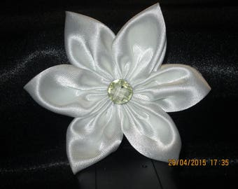 White satin with a flower is adorned with a transparent white button with environments white flower.