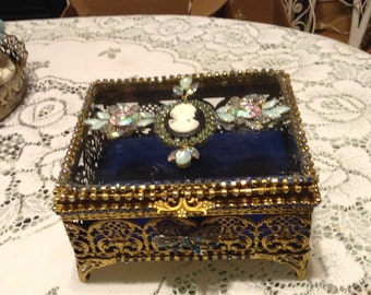 Gold filigree trinket box trimmed in blue with a cameo on top