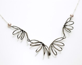 Curved wire necklace with natural pearls