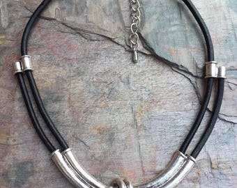 Twisted short iron necklace with double part leather thread, leading to single thread, with extension chain.