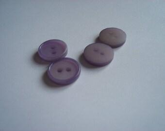 four clear purple plastic buttons