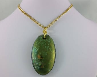 Necklace: green irridescent resin oval pendant on gold chain; faux opal