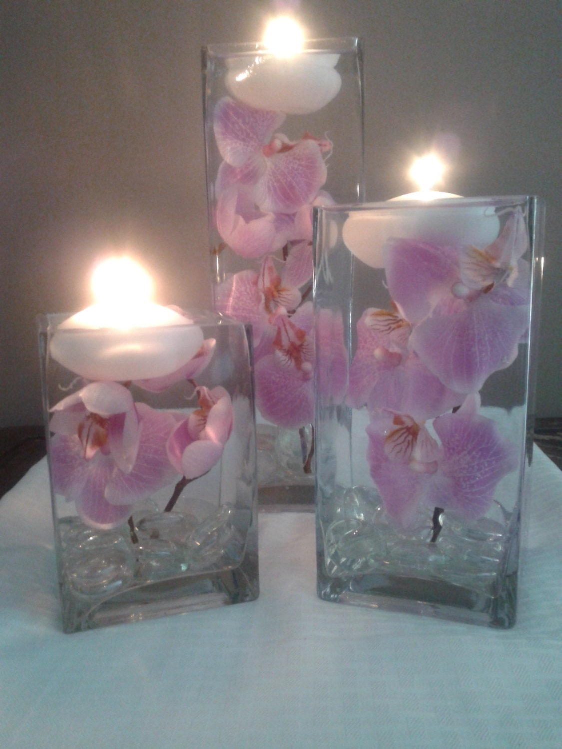 A set of three square vases with purple orchids floating in for How to make flowers float in vases