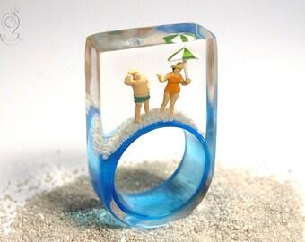 Resort de verano - anillo de figuras de playa de verano con mini figuras, parasol y arena en un anillo de luz azul en resina para el estado de ánimo de vacaciones