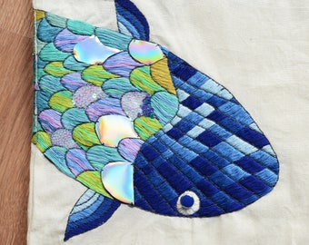 Embroidered fish on off-white tote bag. Usable embroidery design with green, blue, purple, pink threads, buttons, and sequins