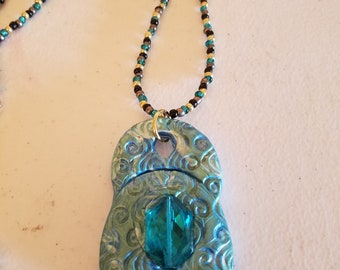 Polymer Clay pendant on a multi-colored seed beaded necklace.