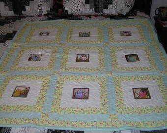 Handmade   lap quilt featuring embroidered garden items