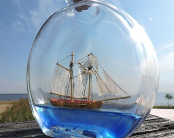 Schooner, ship in a bottle sailing on a blue sea.