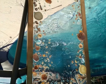 Gold frame with starfish, shells, sea glass, and cat's eyes shells.