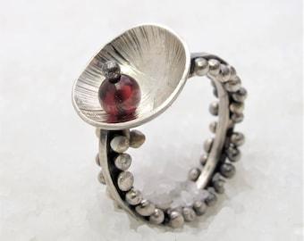 Movement ring, black oxidized silver garnet. Moving pins.