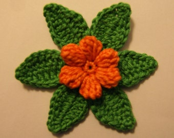 Crocheted applique orange flower with green leaves