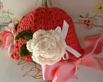 Crochet baby hat in dark pink wool with a rose applied. Children's fashion Idea winter. Romantic and feminine style.