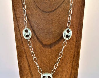 A silver necklace with large mesh and coffee beans