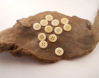 BUTTONS:  12 small cream colored vegetable ivory buttons.  Just under 1/2 inch.