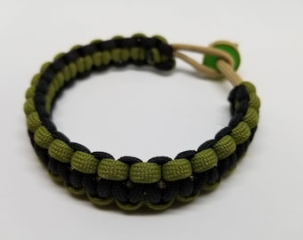Paracord bracelet with recycled 50 caliber shell casing closure