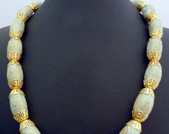 Oval beaded necklace in pale blue and gold swirls