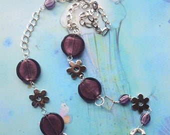 Long metal and glass necklace with silver-coloured flowers and plum-coloured pearls