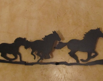 Handcrafted 3 D metal wall art depicts three powerful horses running freely. Beautiful wall accent