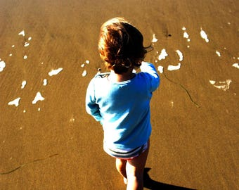 Little Boy walks on the beach