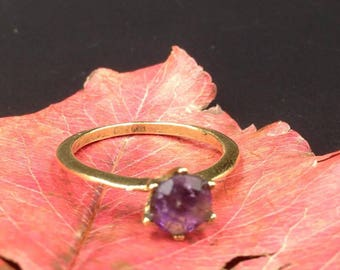 Faceted amethyst in a brass ring.