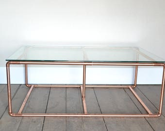 Large glass coffee table on a handmade copper base.