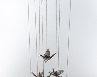 Mobile of origami cranes with dust bunny paper on black butterfly