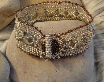 Silver colored glass seed beads woven with Swarovski crystals into this elegant bracelet.  Self loop and toggle closure