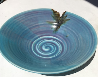 Glazed pottery serving bowl with cutout at rim