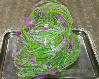 Peeping flowers. Handspun, coilspun, thread plied, beaded art yarn. Cvm, Merino x targhee fleece, locks and abalone shell nuggets. Yummy!