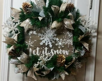 """Let it snow"""" wreath. Greenery base with burlap ,silver and gold ribbons, pinecone and snowflakes. Crystal and glitter snowflakes."""
