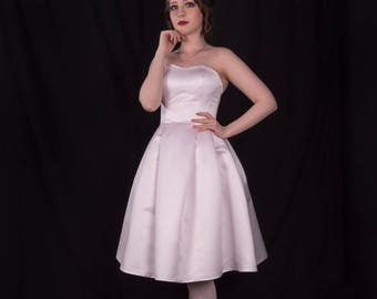 A simplistic strapless tea-length wedding dress with pleats and pockets