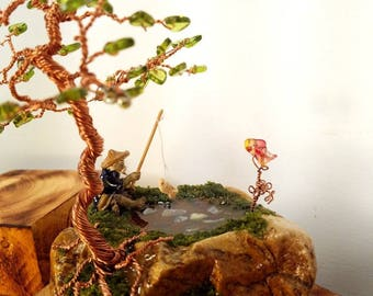 Hand twisted copper tree, decorated with glass leaves and a mudman fishing in the shade