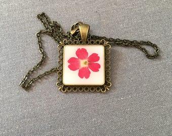 Pink real verdena flower on square decorative bronze pendant