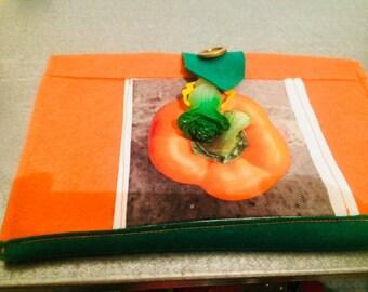 Orange clutch made of felt, ground pepper