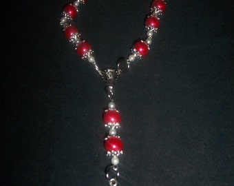 Here a Pretty  Red Bracelet  with Silver Cross