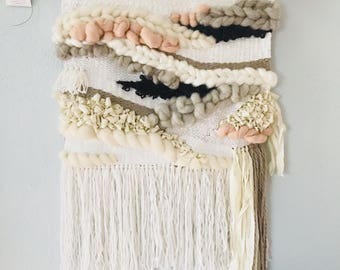 Large textured woven wallhanging in soft neutrals with black accents