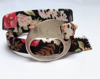 Wrap floral black cotton bracelet with a silver slide fastener and a charm with a black stone.
