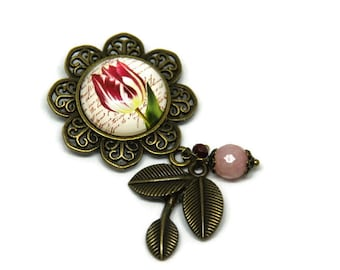 Floral brooch, its pink, red bead and foliage