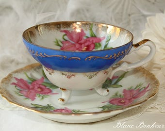 Japan: Three feet blue and pink orchids, tea cup with saucer