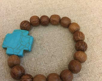 Hand carved wood bead stretch bracelet with turqouise cross accent bead.