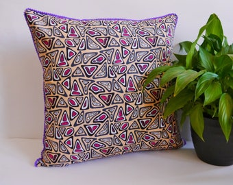 Peach african wax print cushion cover with purple pom pom trim