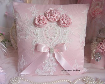 Shabby chic pillow and its silk roses, atmosphere boudoir, powder pink silk and lace embroidered stitching.
