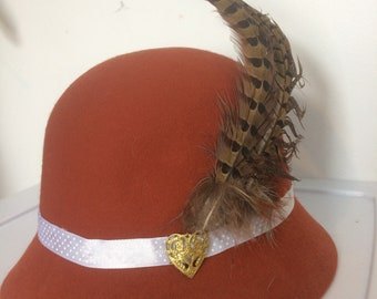 Burnt orange cloche hat with feather
