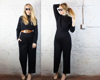 1980's GIRL BOSS solid black turtleneck jumpsuit with pockets in women's medium . gold studs pants sleeves 1970s 70s high fashion