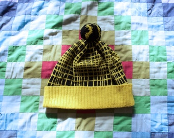 Colourful geometric knitted 'Farpoint' grid design hat with pom-pom. Yellow and black lambswool hat.